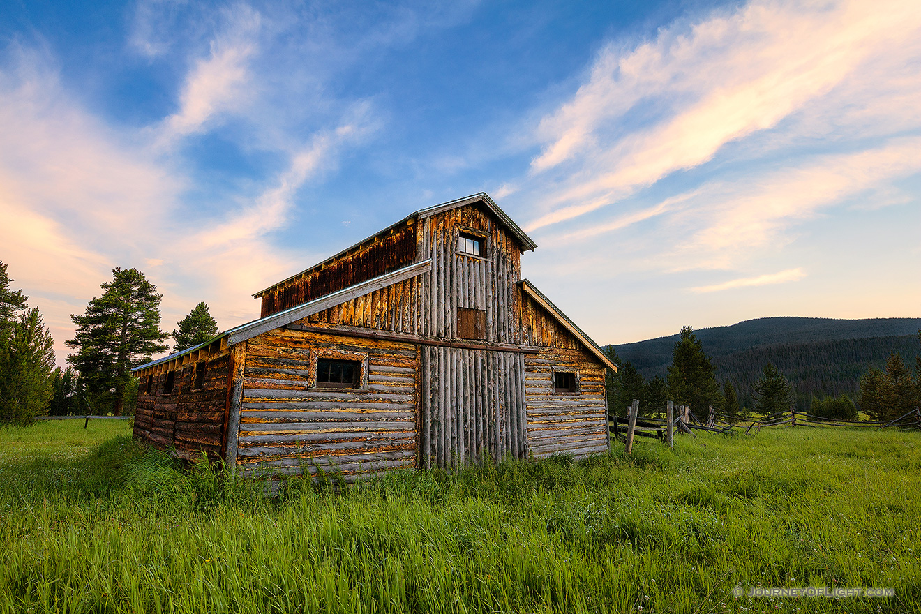 A beautiful wooden barn sits in the Kawuneeche Valley on the western side of Rocky Mountain National Park in Colorado.  Clouds lazily floated by as the sun set behind the Never Summer Range in the distance. - Colorado Picture