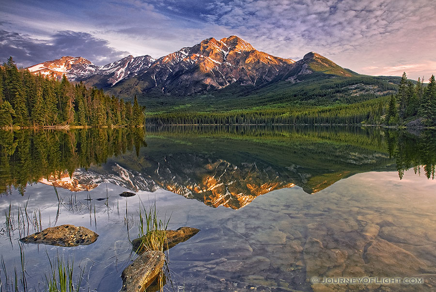 Morning light bathes Pyramid mountain in Jasper National Park.The scene is nearly perfect reflected in the still waters of Pyramid Lake. - Jasper Photography