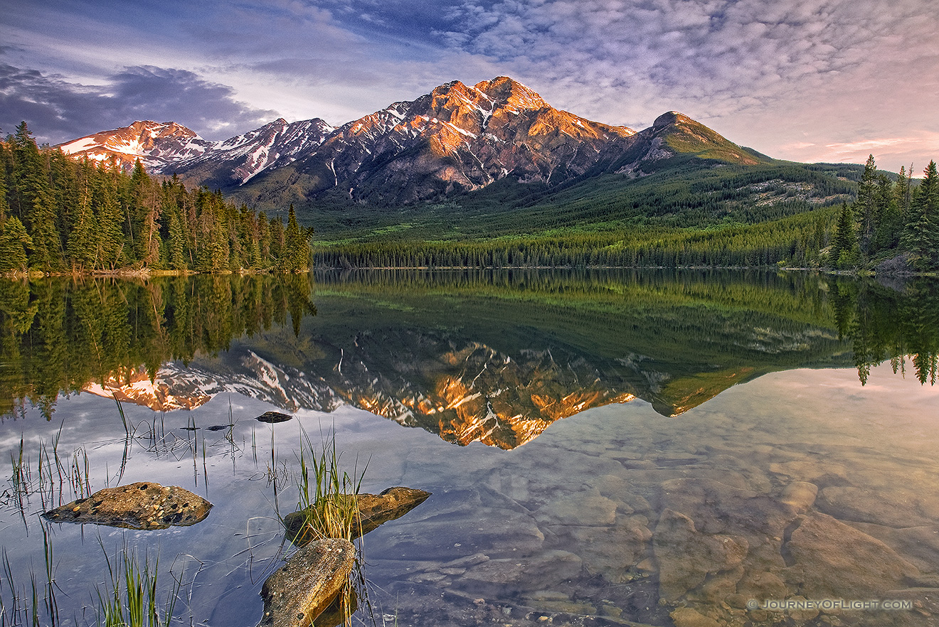 Morning light bathes Pyramid mountain in Jasper National Park.The scene is nearly perfect reflected in the still waters of Pyramid Lake. - Jasper Picture